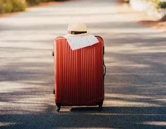 Fotografía de una maleta con un mapa y un sombrero