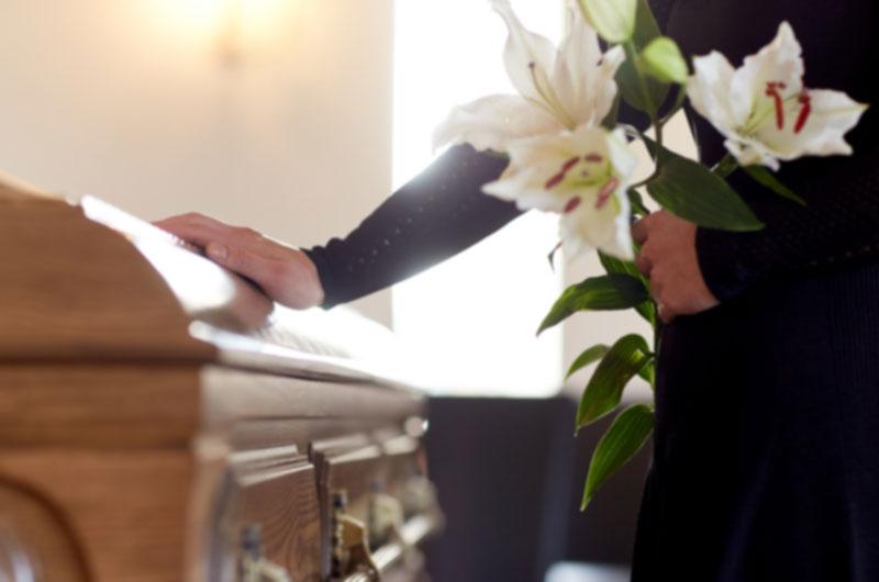 Fotografía de familiar posando su mano en una urna fúnebre