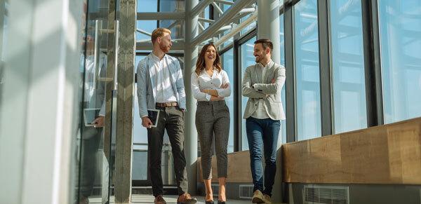 Fotografía de 3 compañeros de trabajo charlando mientras caminan