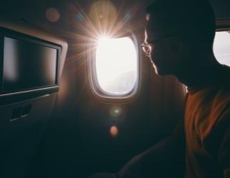 Fotografía de un hombre viendo por la ventanilla de un avión a contra luz