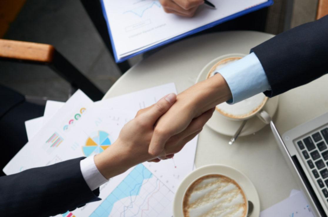 Fotografía de dos personas estrechando la mano cerrando un proyecto